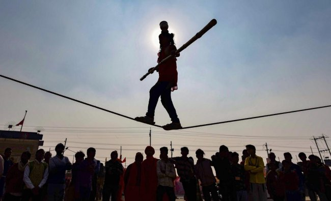 Silhouette of a young girl seen performing stunts as she walks on a tightrope at the Kumbh Mela 2019, in Allahabad. (PTI Photo)