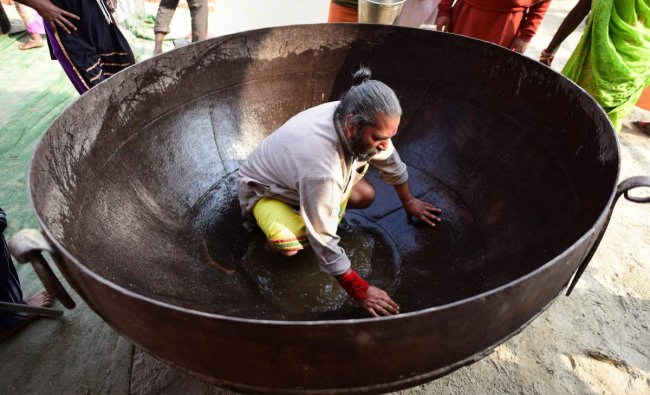A man cleans a huge Kadahi (pan) to be used for cooking food for pilgrims at a camp during the ongoing Kumbh Mela 2019 festival in Allahabad. (PTI Photo)
