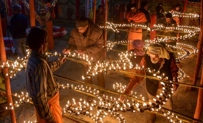 Sadhus along with devotees light oil lamps as a part of evening prayers during Kumbh Mela 2019 in Allahabad. (PTI Photo)