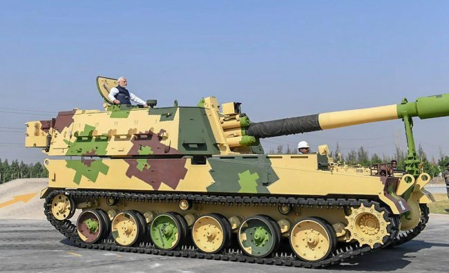 Prime Minister Narendra Modi rides a K-9 Vajra Self Propelled Howitzer built by Larsen & Toubro after the dedication of L&T\'s Armoured System Complex to the nation, in Hajira. (Twitter Photo via PTI)