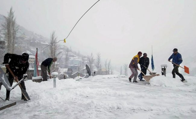 People clear snow outside their houses during fresh snowfall in Lahaul Spiti, Himachal Pradesh. (PTI Photo)