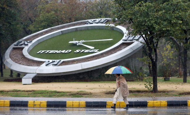 A man holding an umbrella walks in the rain with the backdrop of a giant clock in Islamabad, Pakistan. (Reuters Photo)