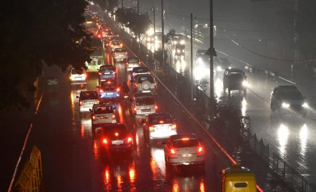 Vehicles ply with their headlights on as visibility gets poor at 08:11 am, during rains in New Delhi. (PTI Photo/Kamal Kishore)