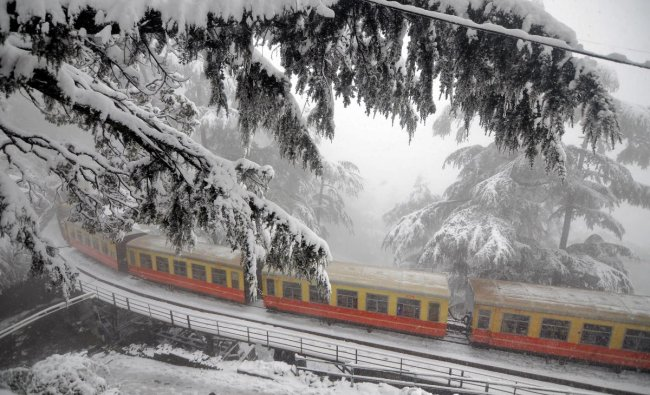 The toy train runs on Kalka-Shimla heritage rail track during heavy snowfall in northern hill town of Shimla. (PTI Photo)