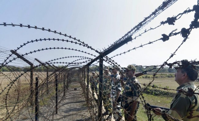 Border Security Force (BSF) personnel patrol along the India- Bangladesh border fencing ahead of the 70th Republic Day function, at Ragna village in Dharmanagar. (PTI Photo)