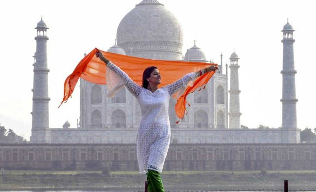 A woman attired in the hues of the Tricolour poses in the backdrop of the Taj Mahal, ahead of Republic Day, in Agra, Friday, Jan. 25, 2019. (PTI Photo)