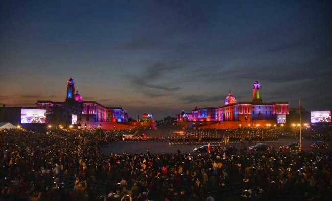 People click pictures of the illuminated Raisina Hills with their mobile phones, after the Beating Retreat ceremony at Vijay Chowk in New Delhi, Tuesday, Jan 29, 2019. (PTI Photo)