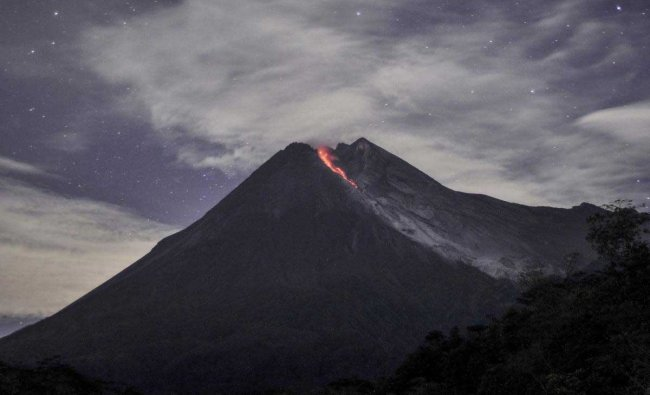 Mount Merapi spews volcanic material as it erupts as seen from Cangkringan, Yogyakarta, Indonesia. Indonesia\'s most volatile volcano has unleashed a 1,400 meters (4,600 feet) dark red volcanic material 1,400 meters (1,500 yards) down the slopes.AP/PTI