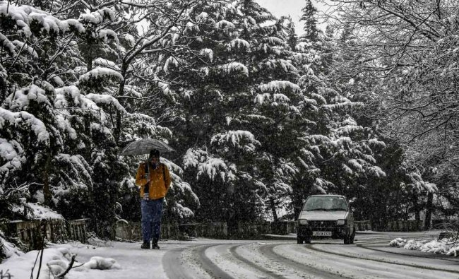 A vehicle moves on a snow-covered road during snowfall in Srinagar, Thursday, January 31, 2019. (PTI Photo)