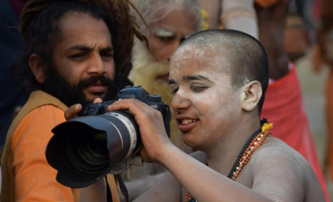 Allahabad: Sadhus shoot on a DSLR camera on a bank of Ganga river during the ongoing Kumbh Mela festival, in Allahabad, Wednesday, Feb 6, 2019. (PTI Photo)