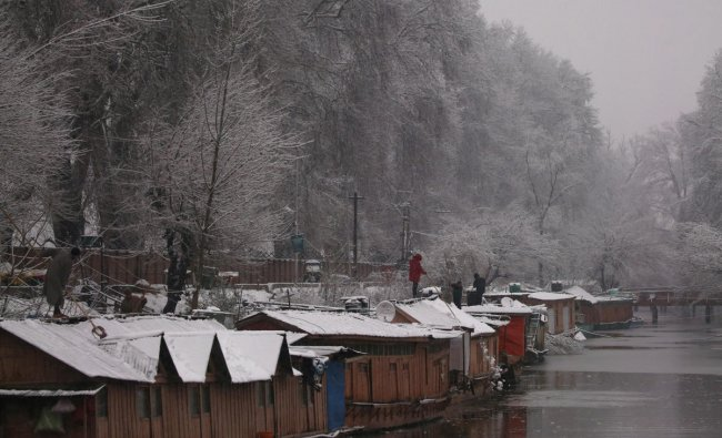 People remove snow from the roofs of their houseboat during a snowfall in Srinagar February 7, 2019. REUTERS/Danish Ismail
