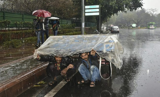 Rickshaw pullers cover themselves during sudden rainfall, in New Delhi, Thursday, Feb 7, 2019. (PTI Photo)