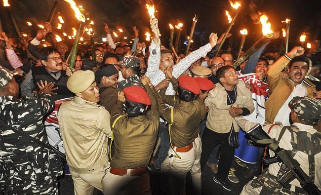 Asom Gana Parishad members clash with police personnel during their torchlight vigil in protest against Citizenship Amendment Bill, in Guwahati, Friday, Feb 8, 2019. (PTI Photo)