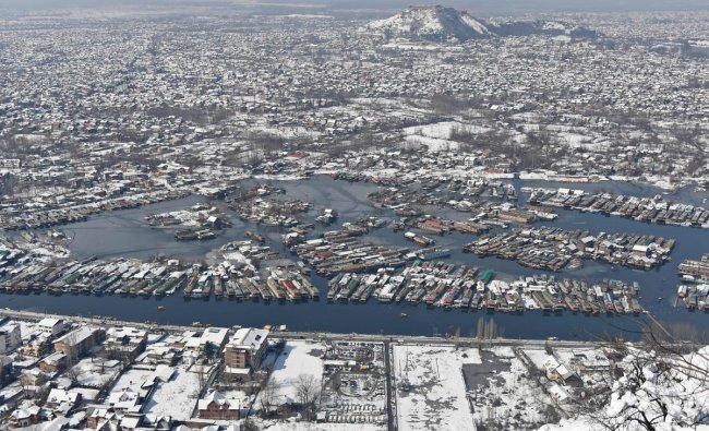 Houses and houseboats covered with snow are pictured from the top of the mountain after a heavy snowfall in Srinagar on February 8, 2019. - Rescuers battled on February 8 to reach the site of an avalanche that buried 10 people in Indian-administered Kashmir following two days of heavy snowfall across the region, police said. (Photo by TAUSEEF MUSTAFA / AFP)