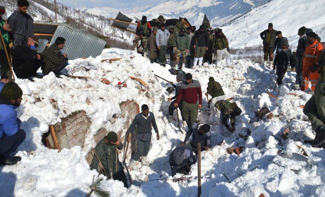 Local residents along with security personnel search the bodies of 10 missing policemen after a snow avalanche hit a police post at Qazigund Jawahar Tunnel in Kulgam district, some 90 km from Srinagar on February 8, 2019. - Three policemen were rescued on February 8 while five other bodies were recovered from an avalanche that buried 10 people in Indian-administered Kashmir following two days of heavy snowfall, police said. (Photo by STR / AFP)