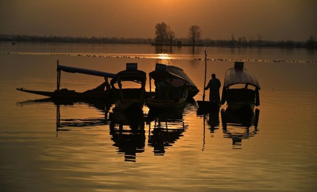 A Kashmiri stands near boats in the middle of Dal Lake at sunset after a heavy snowfall in Srinagar on February 9, 2019. - Beause of recent heavy snowfalls, the roads in Kashmir linking with the rest of India and the Jammu-Srinagar national highway were cut off. (Photo by TAUSEEF MUSTAFA / AFP)