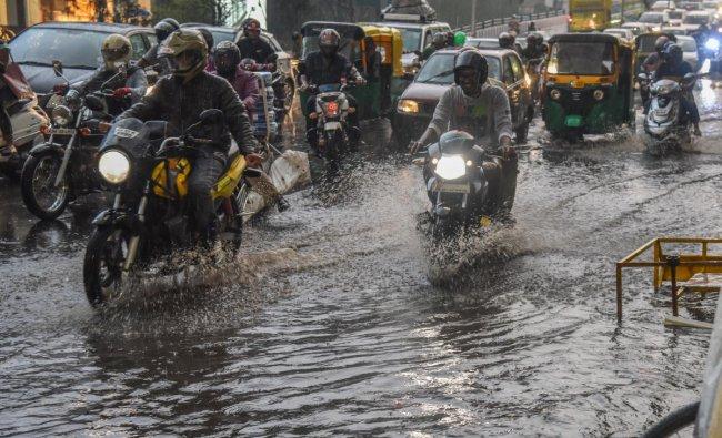 Motorists are raiding vehicle in the rain at Ballari Road in Bengaluru on Saturday evening. DH Photo by S K Dinesh