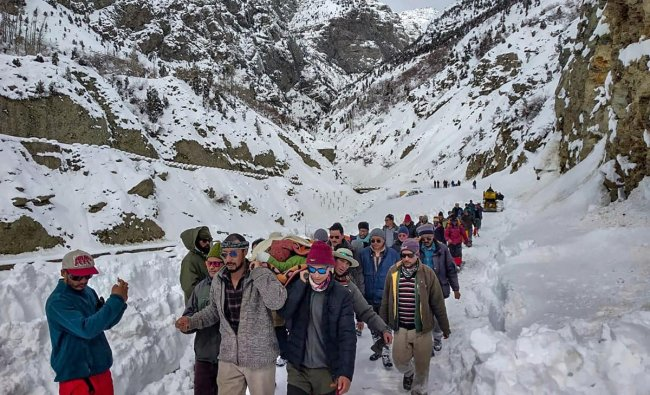 People walk on snow-covered road while carrying a patient to Stingri helipad for treatment, in Lahaul Spiti, Himachal Pradesh, Sunday, Feb 10, 2019. (PTI Photo)