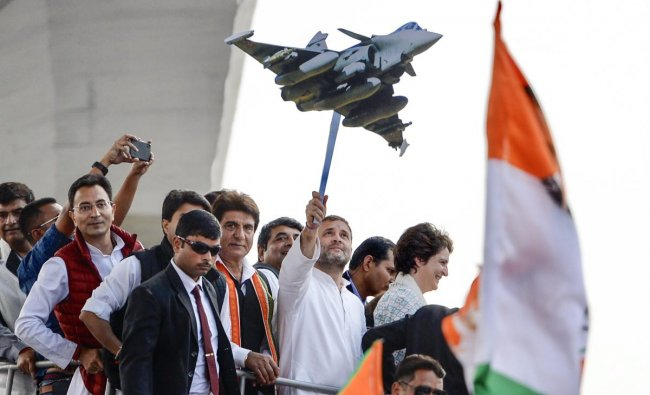 Congress President Rahul Gandhi holds a model of Rafale aircraft during a roadshow along with the party general secretaries Priyanka Gandhi Vadra and Jyotiraditya Scindia, in Lucknow, Monday, Feb. 11, 2019. (PTI Photo)