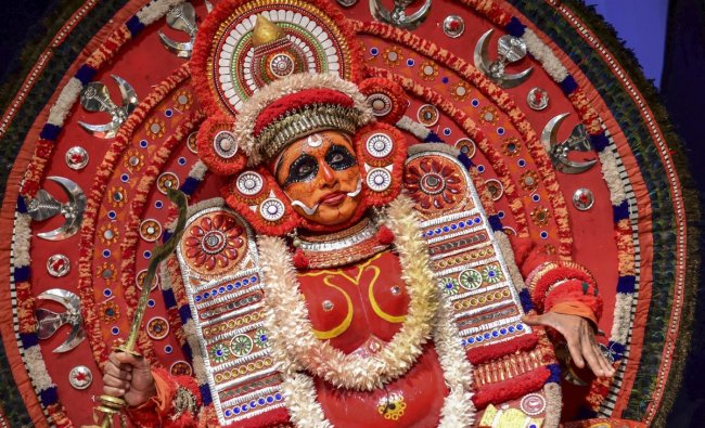 A Theyyam artist poses for photographs before a performance, during a press conference of Kerala Tourism, in Bengaluru, Tuesday, Feb 12, 2019. (PTI Photo/Shailendra Bhojak)