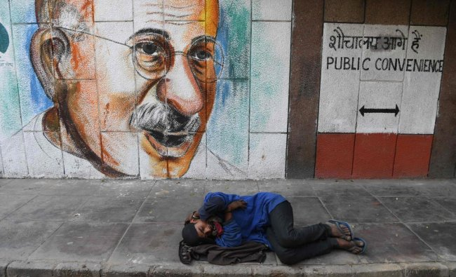 A man sleeps on the ground in front of a mural of Mahatma Gandhi in New Delhi on February 12, 2019. (Photo by Sajjad HUSSAIN / AFP)