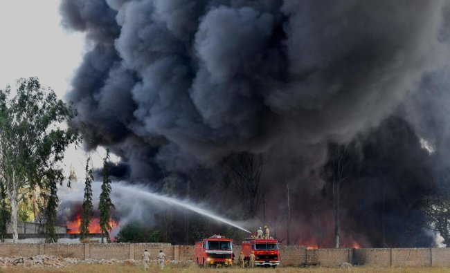 Firefighters battle a massive industrial fire on the grounds of a paint factory on the outskirts of Bangalore on February 13, 2019. - No casualties were reported in the blaze that ignited at the United Paints stockyard in Madanayakanahalli. (Photo by MANJUNATH KIRAN / AFP)