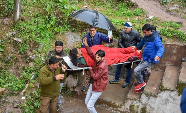 People carry an injured person, after he was wounded due to a shell that was allegedly fired by Pakistan troops along the Line of Control (LoC), in Jammu. PTI