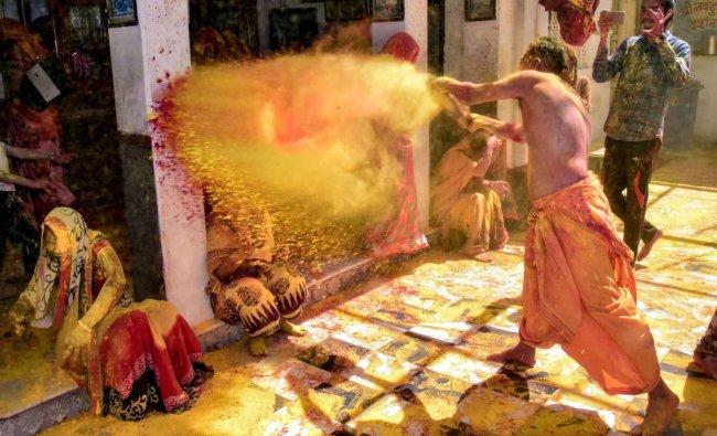 Devotees play Holi at Ghanshyam Ji Temple, ahead of the festival in Jodhpur. PTI