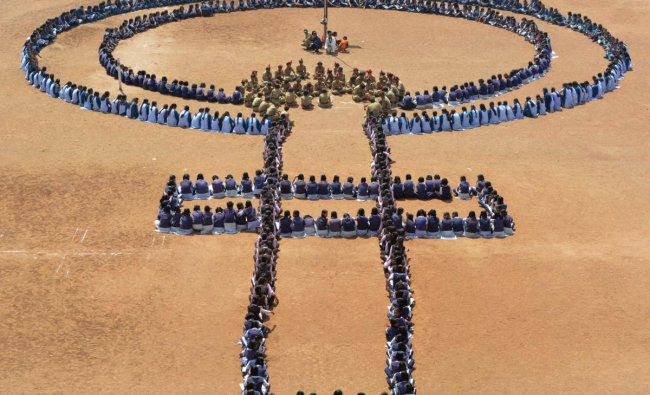 School students create a human chain resembling the women gender symbol, to mark International Women\'s Day, at Rethare village in Karad, Friday, March 8, 2019. (PTI Photo)