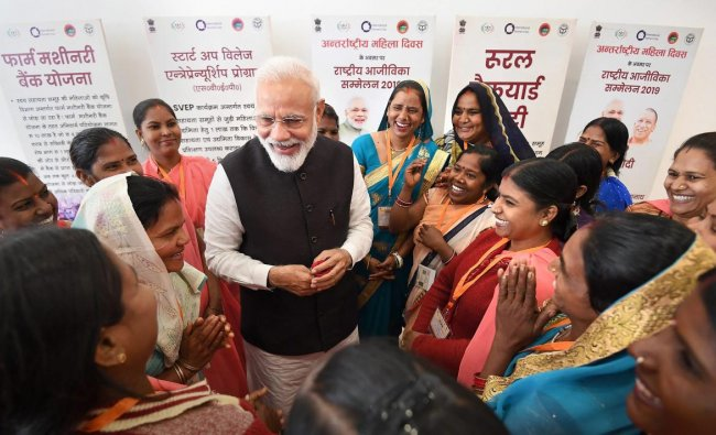 Prime Minister Narendra Modi interacts with the members of Self Help Groups at tthe National Women Livelihood Meet 2019, a programme organised on the occasion of International Women\'s Day, at Deendayal Hastkala Sankul in Varanasi, Friday, March 8, 2019. (PIB/PTI Photo)