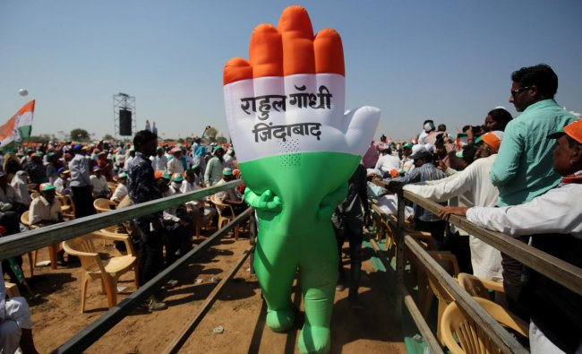 A supporter wearing an inflatable symbol of India\'s main opposition Congress party walks during a public meeting in Gandhinagar, Gujarat, India, March 12, 2019. The words read: \