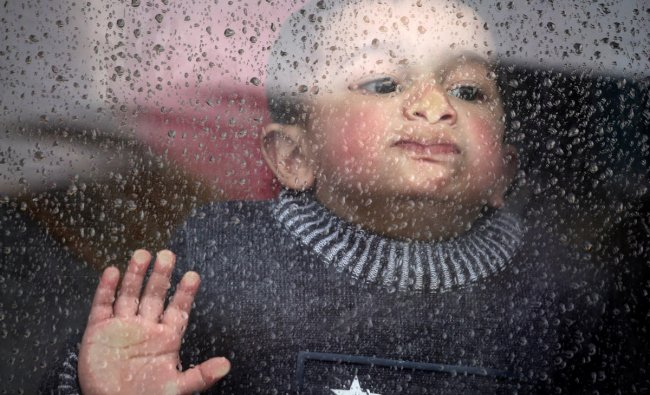 A boy looks out of a car window as it rains in south Kashmir\'s Anantnag district March 13, 2019. REUTERS/Danish Ismail