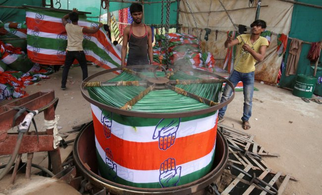 A worker pulls out a roll of cloth from a boiler after dyeing it with the symbol of India\'s main opposition Congress party at a flag manufacturing factory, ahead of the 2019 general elections, in Ahmedabad, India, March 13, 2019. REUTERS/Amit Dave