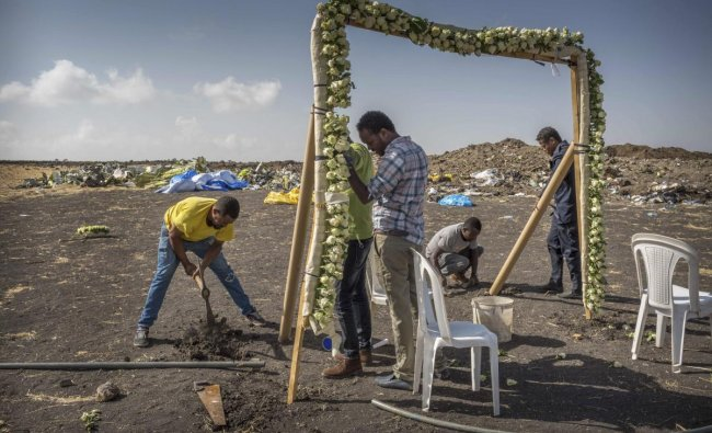 Workers erect floral installations at the scene where the Ethiopian Airlines Boeing 737 Max 8 crashed shortly after takeoff on Sunday killing all 157 on board, near Bishoftu, or Debre Zeit, south of Addis Ababa, in Ethiopia Wednesday, March 13, 2019. AP/PTI