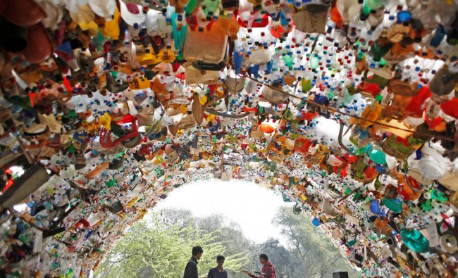 Students perform under a shade made from used plastic bottles as they take part in a global protest against climate change in Gurugram. (Reuters Photo)