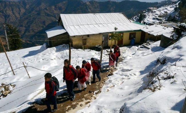 Students walk to school on a snow covered path after fresh snowfall at Kufri near Shimla. (PTI Photo)