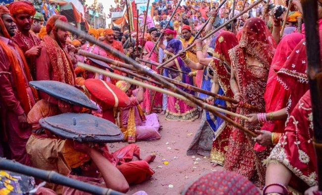 Women beat men with wooden sticks during the \'Lathmar Holi\' festival in Barsana. (PTI Photo)