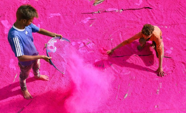 A worker seives coloured powder to be used during the upcoming festival of Holi, at a factory on the outskirts of Jabalpur. (PTI Photo)