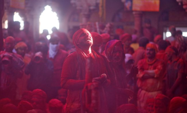 A man daubed in colours sings religious hymns as he takes part in \