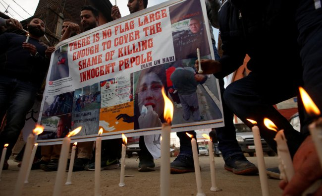 People light candles as they hold a banner during a protest against Friday\'s mosque attacks in New Zealand, in Srinagar. (Reuters Photo)