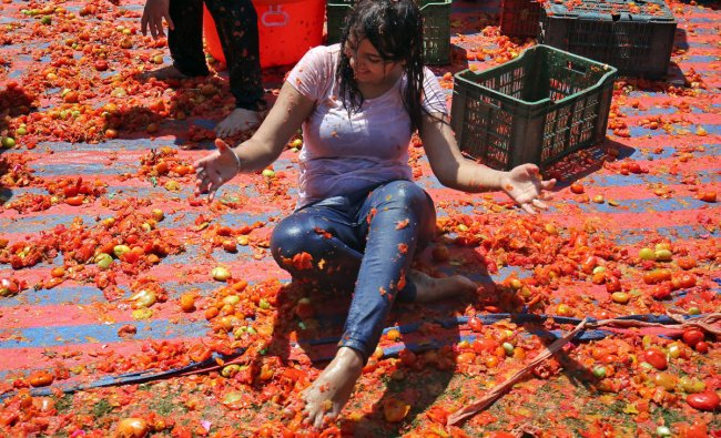 A woman reacts as she is covered with tomato pulp during Holi celebrations in Ahmedabad. (Reuters Photo)