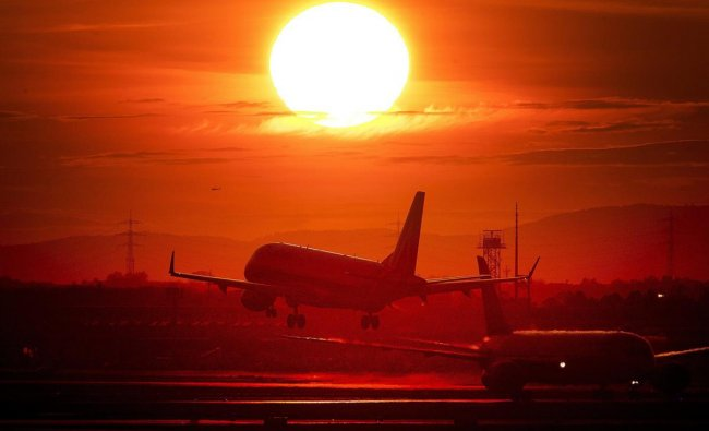 An aircraft lands at the international airport in Frankfurt, Germany, as the sun sets. (AP/PTI Photo)