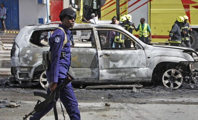A member of security forces walks past the burned-out vehicle after a bomb planted in it exploded in Mogadishu, Somalia Tuesday, March 26, 2019. A Somali police officer says the bomb exploded killing the driver and injuring a nearby pedestrian in the Hodan district of the capital. AP/PTI