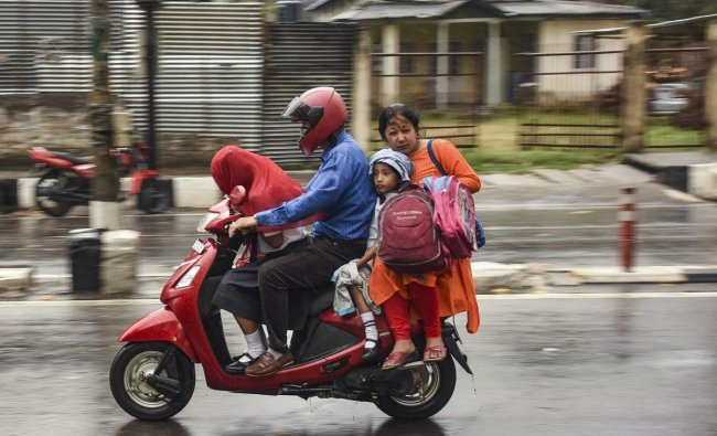A family travels on a two-wheeler during rains in Guwahati, Tuesday, March 26, 2019. (PTI Photo)