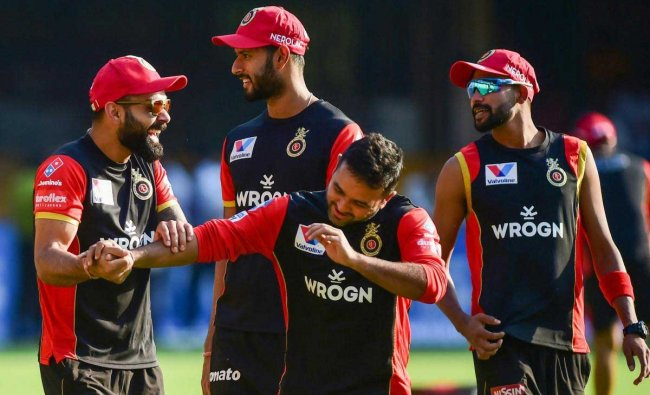 Royal Challengers Bangalore\'s Skipper Virat Kohli with teammate Parthiv Patel and others share a lighter moment during their training session ahead of the Indian Premier League 2019 (IPL T20) cricket match between Royal Challengers Bangalore (RCB) and Mumbai Indians (MI), at Chinnaswamy Stadium in Bengaluru, Wednesday, March 27, 2019. (PTI Photo)