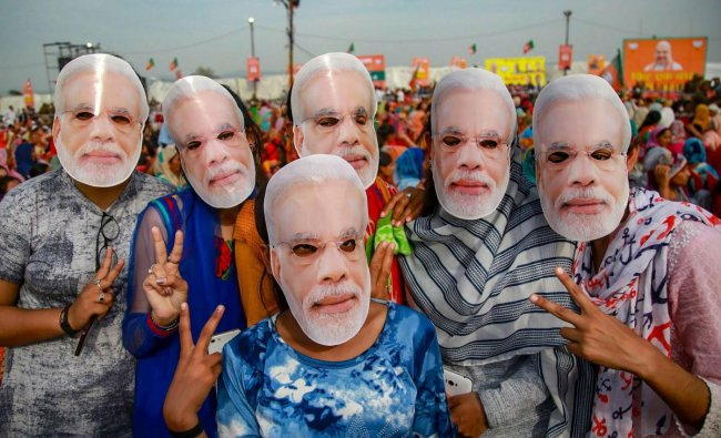BJP supporters wear masks of Prime Minister Narendra Modi to extend their support during a public rally ahead of Lok Sabha elections, at Dumi village near Jammu, Thursday, March 28, 2019. (PTI Photo)