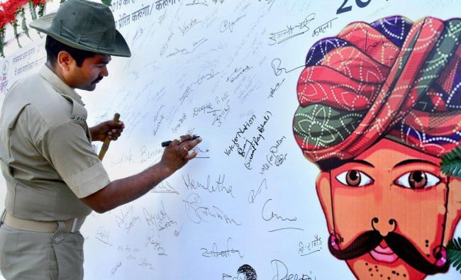 A Rajasthan Armed Constabulary (RAC) jawan puts his signature on a banner during an election awareness campaign, in Bikaner, Friday, April 05, 2019. (PTI Photo)