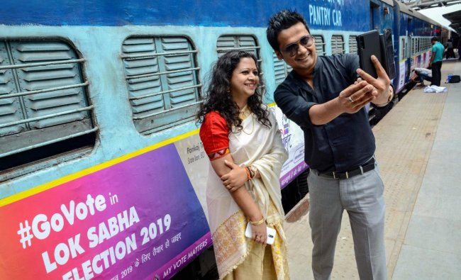 Actor Kopil Bora and singer Tarali Sarma take selfie near the Guwahati-Okha Dwarka Express which is branded with systematic voters education and electoral participation messages for the Lok Sabha polls, before it was flagged off at Guwahati Railway station in Guwahati, Monday, April 8, 2019. (PTI Photo)