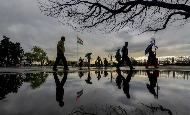 People take a stroll as dark clouds hover in the sky, in Shimla, Monday, April 08, 2018. (PTI Photo)
