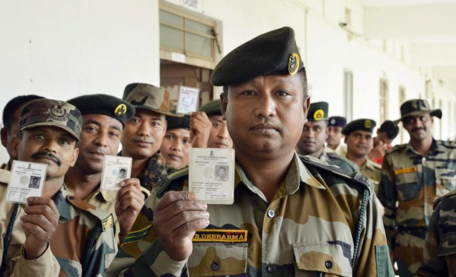 Tripura State Rifles personnel show their voter identity cards before casting their votes through postal ballots for the Lok Sabha elections, in Dharmanagar, Manday, April 8, 2019. (PTI Photo)